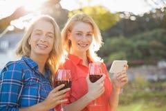 Belles femmes tenant des verres du vin rouge et du téléphone portable Photos libres de droits