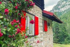 Belles fenêtres en bois rouges d'une hutte de montagne Photographie stock