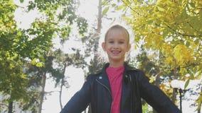 Belles feuilles de lancement de jeune fille en parc, appréciant Concept de loisirs de liberté de bonheur Enfant détendant en auto banque de vidéos