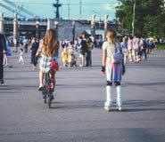 Belles filles à la mode sur des rouleaux et sur une bicyclette photo stock