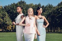 Belles filles élégantes posant sur le terrain de golf avec l'herbe verte et les miroirs Image libre de droits