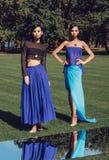 Belles filles élégantes posant sur le terrain de golf avec l'herbe verte et les miroirs Photos stock