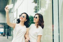 Belles filles asiatiques avec des paniers prenant la photo de selfie à Photo libre de droits