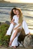 Belles filles au-dessus de fond de coucher du soleil Photographie stock libre de droits