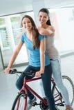 Belles filles avec une bicyclette rouge Photographie stock libre de droits