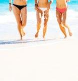 Belles filles ayant l'amusement marchant sur la plage Photo stock