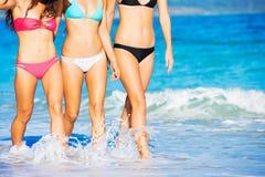 Belles filles ayant l'amusement marchant sur la plage Photographie stock libre de droits