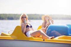 Belles filles détendant sur le bateau de palette Photographie stock