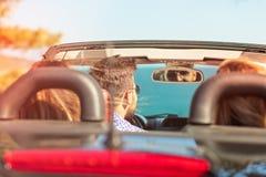 Belles filles d'ami de partie dansant dans une voiture sur la plage heureuse Photo stock