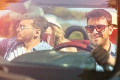Belles filles d'ami de partie dansant dans une voiture sur la plage heureuse Image stock