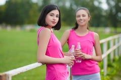 Belles filles d'athlète de forme physique se reposant ou eau potable extérieure Images libres de droits