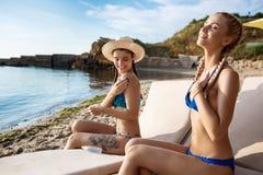 Belles filles dans le sourire de vêtements de bain, appliquant la crème de bronzage au bord de la mer Photos stock