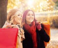 Belles filles marchant en parc avec les sacs colorés Photo libre de droits