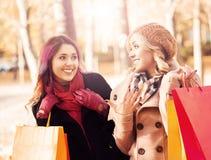 Belles filles marchant en parc avec les sacs colorés Photo stock