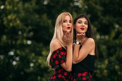 Belles filles posant pour le photographe Deux soeurs dans la robe noire et rouge Sourire, jour ensoleillé, été Photo stock