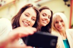 Belles filles prenant la photo en café dans la ville Image stock
