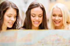 Belles filles regardant dans la carte de touristes dans la ville Images libres de droits