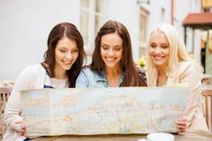 Belles filles regardant dans la carte de touristes dans la ville Image libre de droits