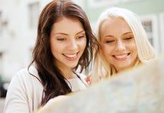 Belles filles regardant dans la carte de touristes dans la ville Photographie stock