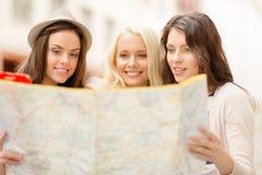 Belles filles regardant dans la carte de touristes dans la ville Photos libres de droits