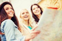 Belles filles regardant dans la carte de touristes dans la ville Image stock