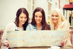 Belles filles regardant dans la carte de touristes dans la ville Photo stock