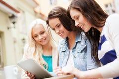 Belles filles regardant le PC de comprimé en café Photo stock