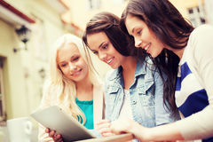 Belles filles regardant le PC de comprimé en café Photographie stock libre de droits