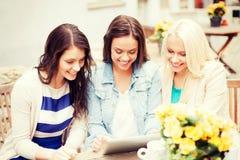 Belles filles regardant le PC de comprimé en café Photos stock