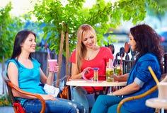 Belles filles s'asseyant sur la terrasse de café Photographie stock