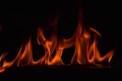Belles flammes du feu sur le fond noir Images stock