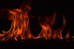 Belles flammes du feu sur le fond noir Photo libre de droits