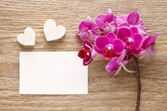 Belles fleurs d'orchidée et feuille de papier roses sur le bois Photos stock
