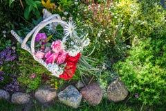 Belles fleurs dans le panier blanc dans le jardin ensoleillé Image stock