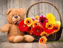 Belles fleurs dans le panier et un ours de nounours Photos stock