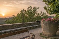 Belles fleurs dans un pot en pierre avec le coucher du soleil et une pose femelle sur la roche photographie stock libre de droits