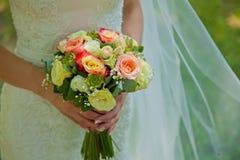 Belles fleurs de mariage dans des mains de jeune mariée Fond Photo stock