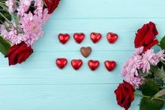 Belles fleurs et chocolat en forme de coeur Photos stock