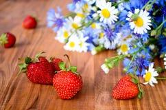 Belles fleurs sauvages et fraises fraîches Photographie stock