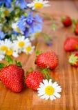 Belles fleurs sauvages et fraises fraîches Images stock