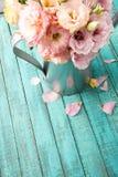 Belles fleurs tendres dans la boîte d'arrosage et des pétales roses sur la surface en bois Image stock