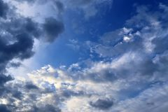 Belles formations mélangées de nuage avec les cumulus blancs et gris à la lumière du soleil sur un ciel bleu image stock