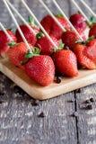 Belles fraises de fraises rouges fraîches de fraises sur des fraises de brochettes sur la photo de verticale de conseil en bois Photo stock