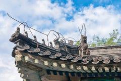 Belles gouttières chinoises avec le dragon et d'autres sculptures symboliques en tuile Images stock