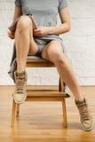 Belles jambes d'une femme lisant un journal Photographie stock libre de droits