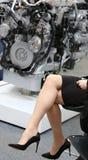 Belles jambes de femme à côté d'un moteur puissant photographie stock