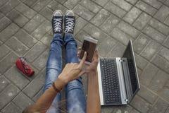 Belles jambes de femme avec le téléphone, ordinateur portable, verres sur le trottoir Photographie stock libre de droits