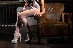 Belles jambes de femme dans les bas blancs sur des talons hauts photo stock