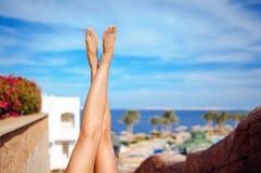 Belles jambes de fille sur un fond de ciel bleu Images libres de droits