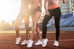 Belles jambes de trois femmes convenables d'athlète au stade Photos stock